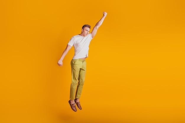 Retrato do super-herói louco pula, levanta o punho, voa sobre fundo amarelo
