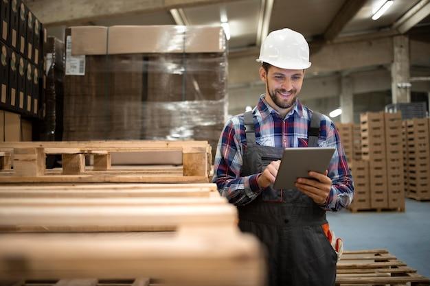 Retrato do supervisor do trabalhador de armazenamento digitando no tablet e organizando a chegada de novas mercadorias ao armazém.
