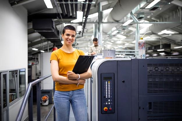 Retrato do talentoso designer feminino parado perto da moderna máquina de impressão na gráfica.