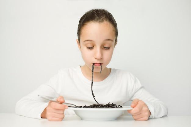 Retrato do tipo espanhol em uma camisa branca de frente para o lado comendo espaguete preto em uma parede branca