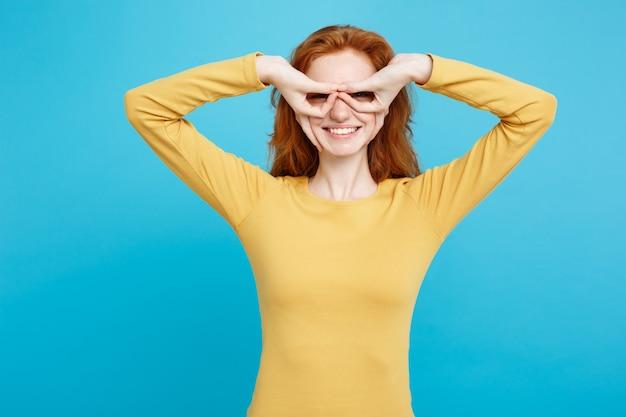 Retrato do tiro na cabeça do conceito de diversão e pessoas de uma garota ruiva ruiva feliz com sardas sorrindo e fazendo óculos de dedo na parede azul pastel.