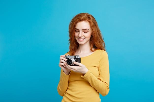 Retrato do tiro na cabeça do conceito de viagens e pessoas de uma garota ruiva ruiva feliz pronta para viajar com uma câmera vintage em um espaço de cópia de parede azul pastel de expressão feliz