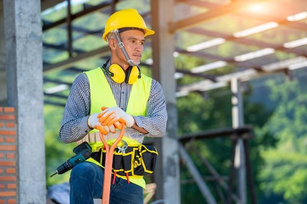 Retrato do trabalhador da construção civil em pé no canteiro de obras.