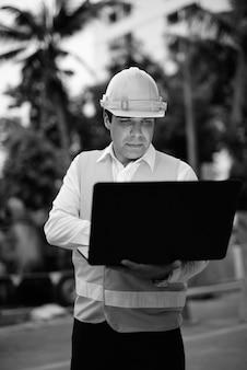 Retrato do trabalhador da construção civil persa bonito no canteiro de obras em preto e branco