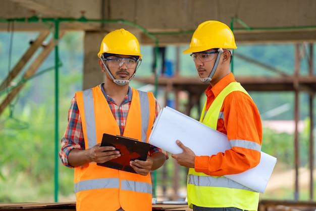 Retrato do trabalhador da construção seguro no canteiro de obras, conceito do negócio do contratante de construção dos bens imobiliários.