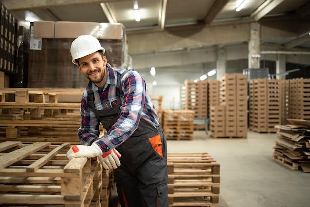 Retrato do trabalhador do armazém apoiado na paleta de madeira na sala de armazenamento da fábrica.
