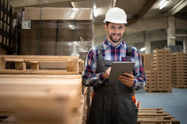 Retrato do trabalhador do armazém digitando no computador tablet e aguardando a paleta de madeira na sala de armazenamento da fábrica.