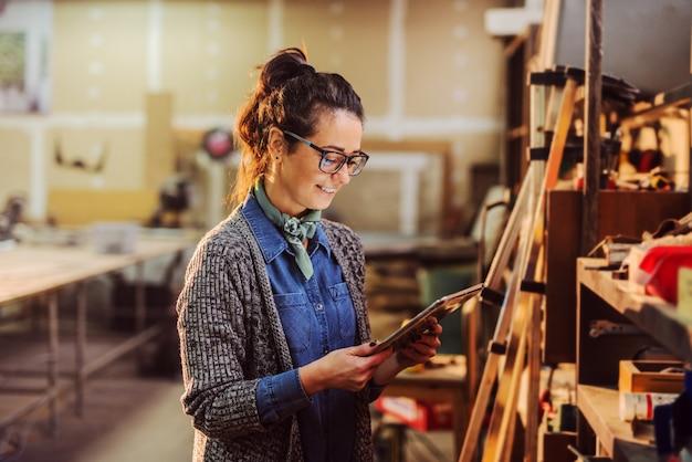 Retrato do trabalhador fêmea da indústria bonita da idade média que guarda a tabuleta em suas mãos e que está na frente da prateleira com ferramentas.
