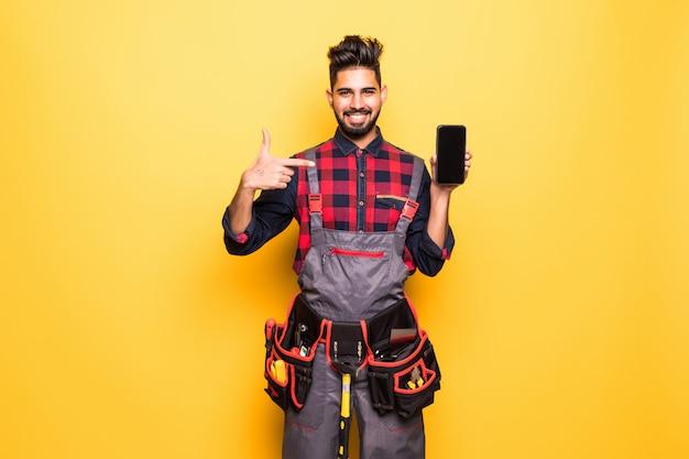 Retrato do trabalhador manual indiano sorridente, mostrando a tela do telefone móvel em espaço amarelo