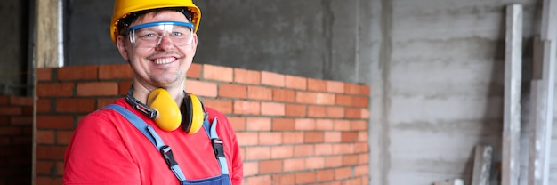 Retrato do trabalho construtor ou engenheiro escrevendo informações na área de transferência. homem usando capacete, óculos e luvas.
