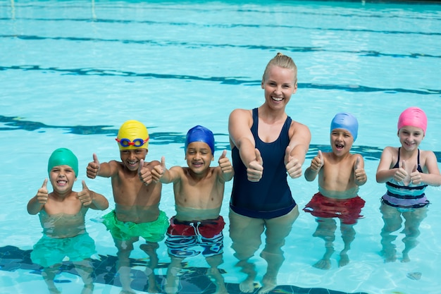 Retrato do treinador e crianças mostrando os polegares na piscina