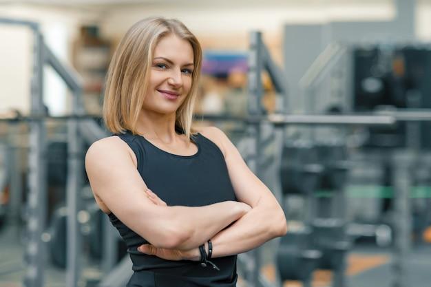 Retrato do treinador pessoal da mulher loira adulta fitness