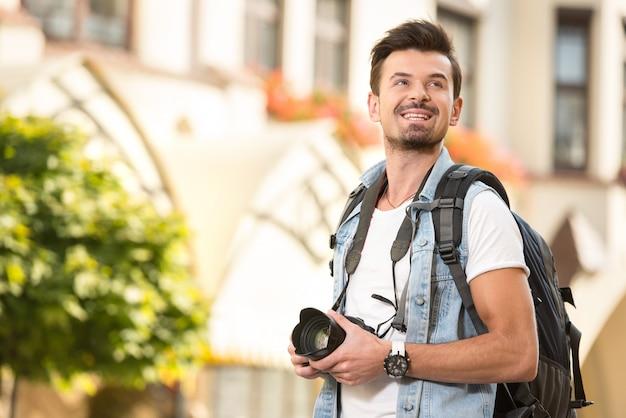 Retrato do turista novo feliz com a câmera na cidade.