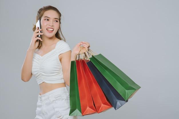 Retrato do uso asiático da mulher do telefone móvel e de guardar o saco de compras. sorriso feliz da menina após ter comprado sobre o cinza no estúdio.