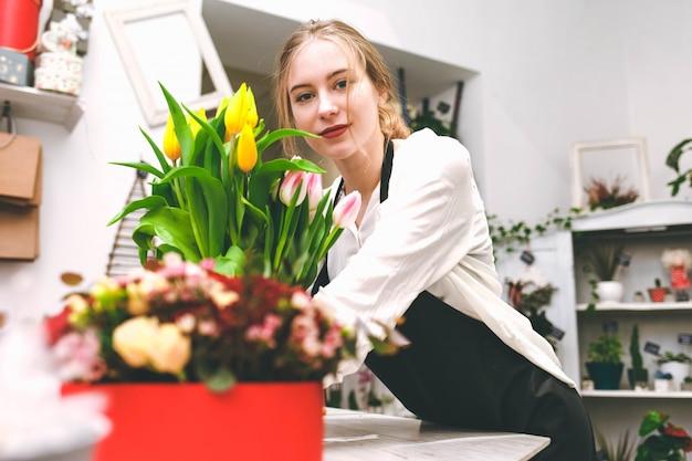 Retrato do vendedor de flores jovem no balcão da loja.