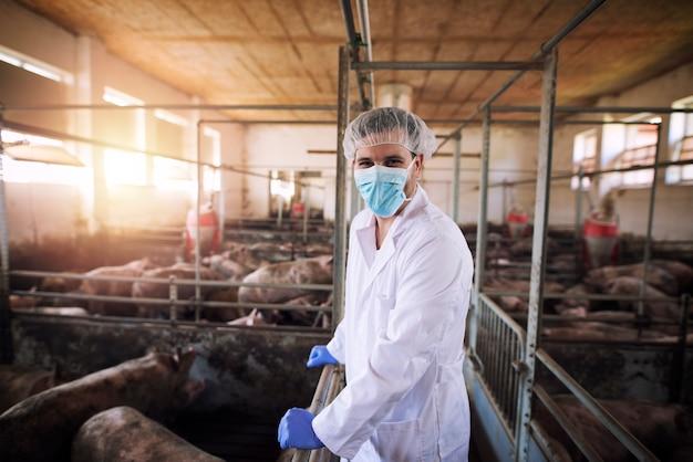 Retrato do veterinário em traje de proteção branco com rede para o cabelo e máscara em pé no chiqueiro, observando animais domésticos na fazenda de porcos.