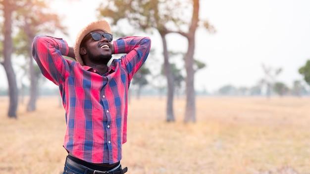 Retrato do viajante africano que sorri e que aprecia seu tempo da recreação na natureza. conceito do dia do turismo