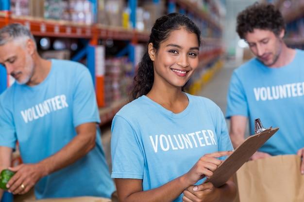 Retrato do voluntário sorridente segurando a área de transferência
