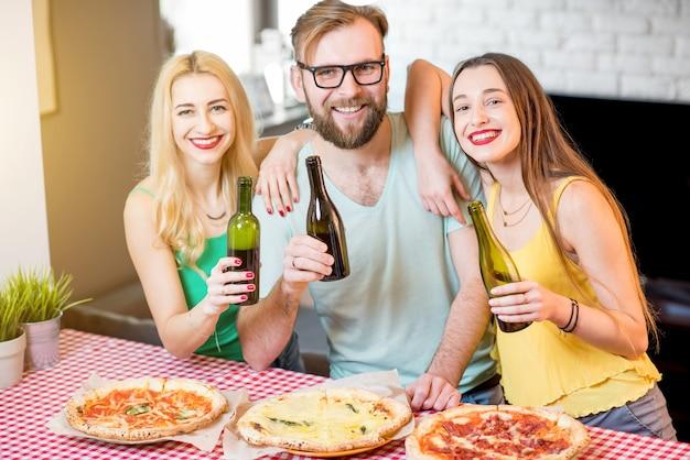 Retrato dos jovens amigos vestidos casualmente com camisetas coloridas almoçando com pizza e cerveja em casa