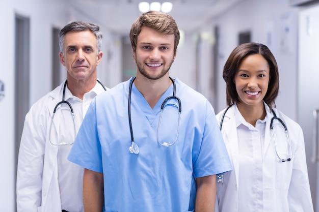 Retrato dos médicos sorridentes em pé no corredor