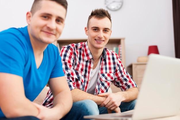 Retrato dos melhores amigos com laptop em casa