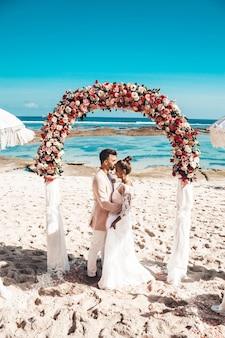 Retrato dos noivos que levantam perto do arco tropical do casamento na praia atrás do céu azul e do mar. casal de noivos