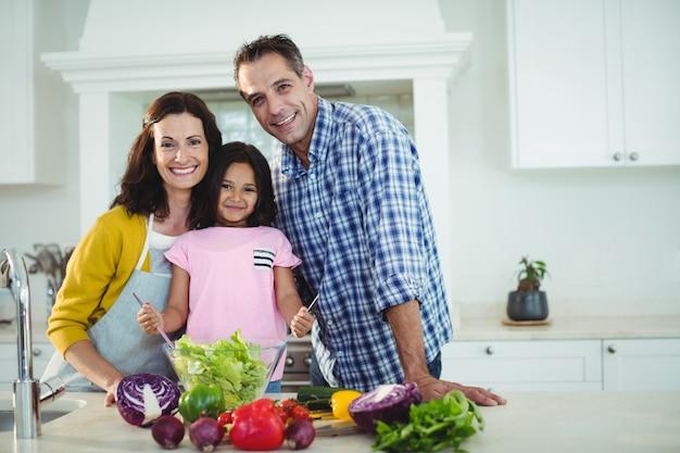 Retrato dos pais e filha preparando salada na cozinha