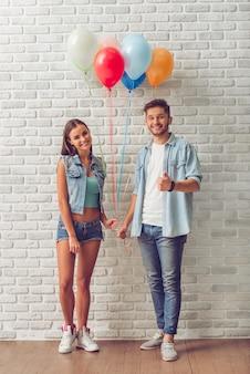 Retrato dos pares adolescentes à moda que guardam balões.