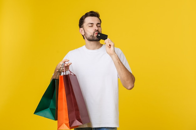 Retrato dos pares de sorriso que mantêm sacos de compras e cartão de crédito isolados no amarelo.