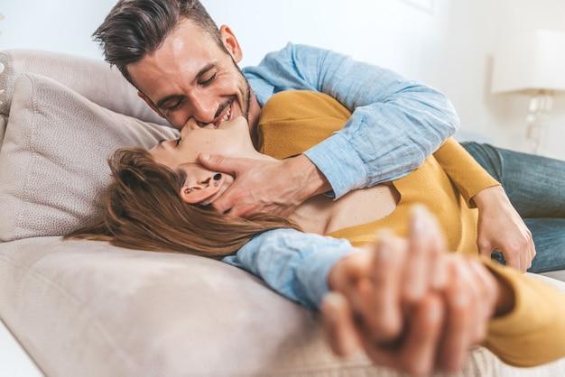 Retrato dos pares românticos que afagam e que beijam guardando as mãos que encontram-se no sofá na sala de visitas em casa.