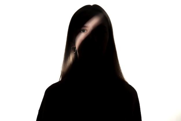 Retrato dramático de jovem no escuro, isolado na parede branca do estúdio