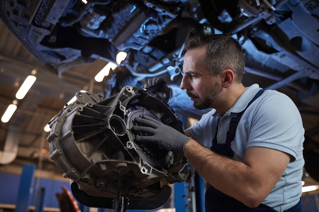 Retrato dramático de um mecânico de automóveis musculoso inspecionando a peça do carro em uma oficina mecânica, copie o espaço