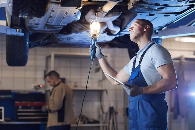 Retrato dramático de um mecânico musculoso sob o carro no elevador enquanto inspeciona o veículo na oficina mecânica, copie o espaço