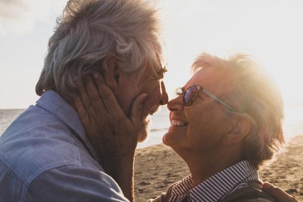Retrato e close-up de dois idosos apaixonados dançando e sorrindo com o sol do pôr do sol entre suas cabeças