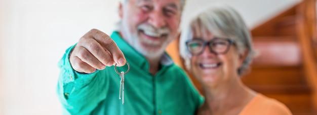 Retrato e close-up de dois idosos felizes comprando uma casa nova segurando a chave com a mão