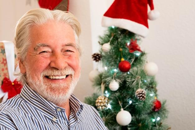 Retrato e close-up de um homem maduro, sorrindo e rindo, olhando para a câmera com uma árvore de natal ao fundo - idosos aposentados no dia de natal em casa