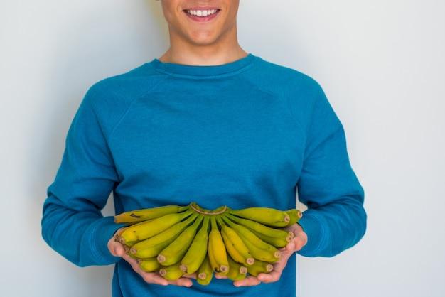 Retrato e close-up de um homem ou adolescente ou menino segurando um monte de bananas e sorrindo, olhando para a câmera - segurando frutas - estilo de vida saudável e conceito e propriedades da banana