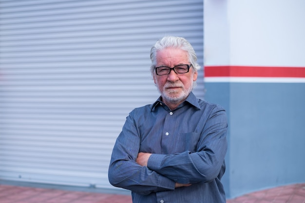 Retrato e close-up de um homem velho olhando para a câmera com a loja fechada para o bloqueio de quarentena na parte de trás - homem de negócios profissional