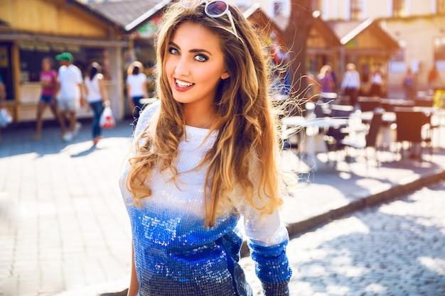 Retrato elegante da cidade de mulher bonita posando para o dia de outono agradável outono ensolarado formiga de rua. usando óculos escuros e suéter casual azul brilhante.