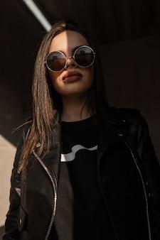 Retrato elegante de um modelo de mulher jovem e bonita com roupas da moda de couro preto com uma jaqueta e óculos de sol vintage ao ar livre. foto criativa com luz do sol e sombra
