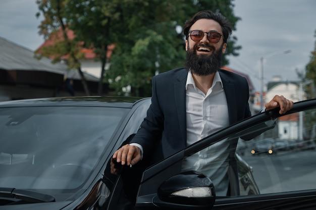 Retrato elegante e bonito homem perto de carro ao ar livre
