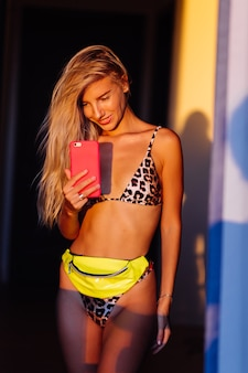 Retrato elegante e colorido de jovem apto magro blogueira em biquíni de leopardo na luz do sol quente tirar foto