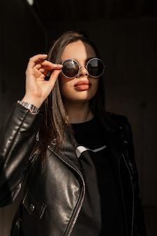 Retrato elegante e criativo de uma mulher bonita e jovem hippie com uma jaqueta de couro elegante e óculos de sol redondos sob a luz do sol e sombra ao pôr do sol