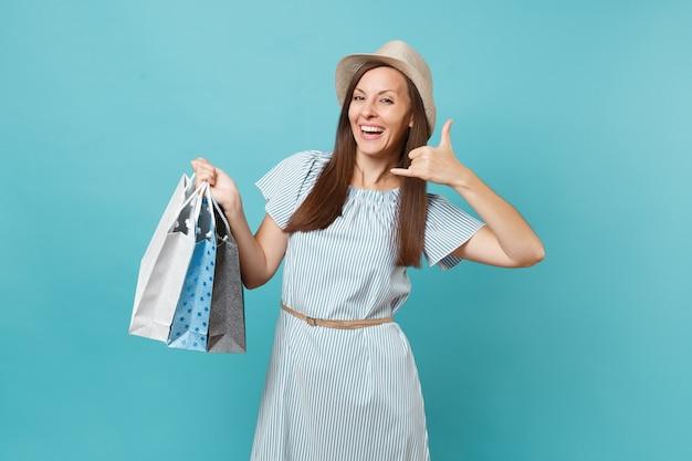 Retrato elegante sorridente linda mulher caucasiana com vestido de verão, chapéu de palha segurando sacolas de pacotes com compras após as compras isoladas em fundo azul pastel. copie o espaço para anúncio.