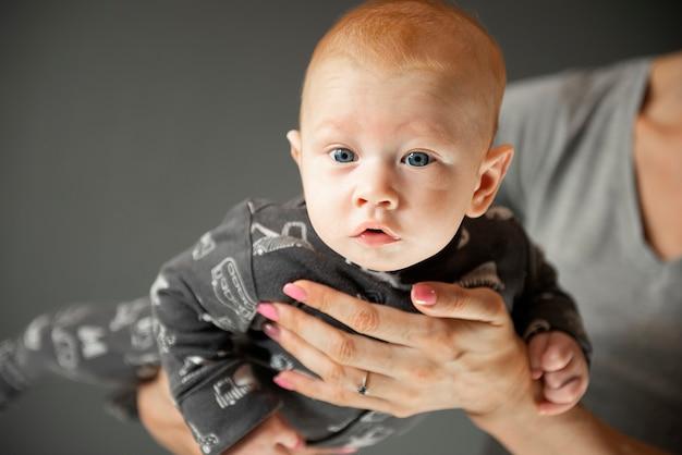 Retrato em close de um menino recém-nascido, que a mãe segura nos braços