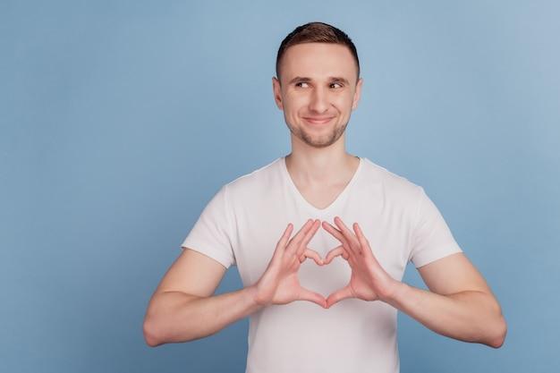 Retrato em close-up de cara feliz, sorrindo, mostrando uma figura de coração curiosa, olhar o espaço vazio isolado sobre um fundo azul