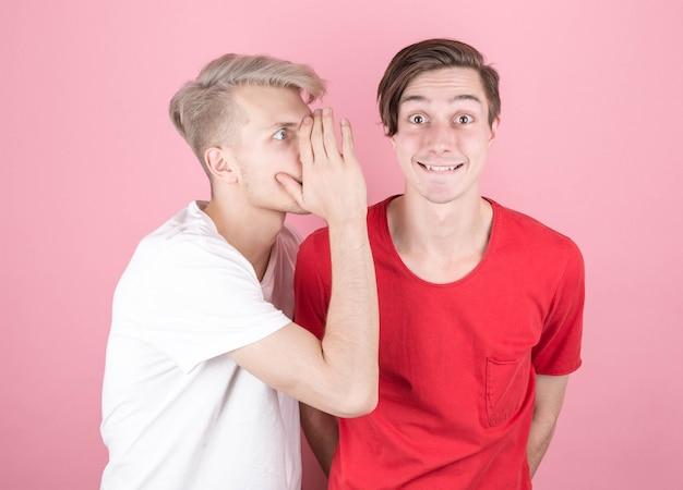 Retrato em close-up de dois jovens, um sussurrando segredos para o outro, chocados e muito surpresos, com a boca escancarada na cor rosa
