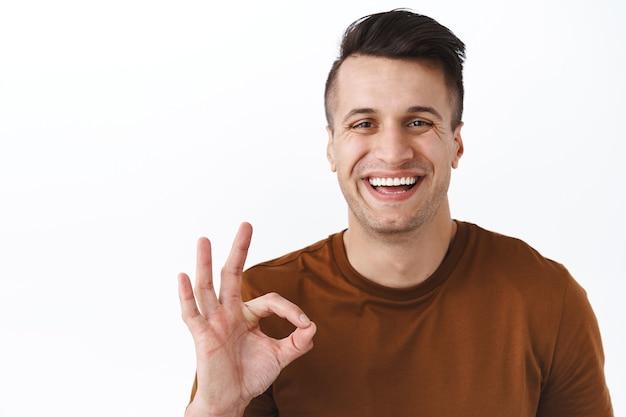 Retrato em close-up de homem adulto bonito satisfeito garantindo melhor qualidade, sorrindo e rindo satisfeito, mostrar sinal de bom, recomendar usar assinatura, aprovar ou gostar de escolha excelente