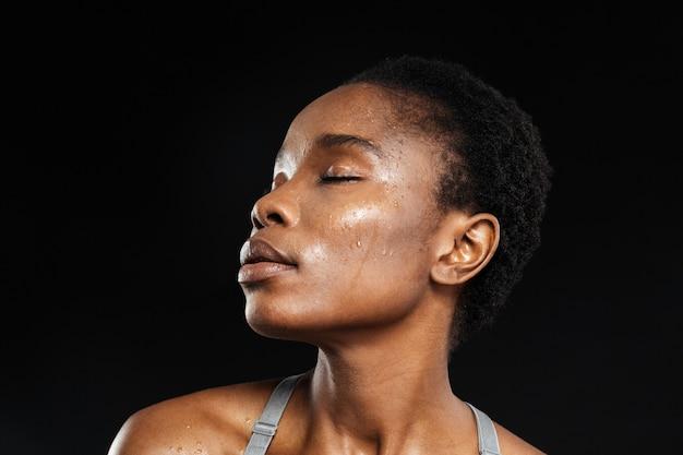 Retrato em close-up de mulher com pele fresca e olhos fechados, isolado em uma parede preta