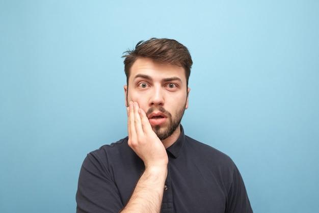 Retrato em close-up de um barbudo surpreso que cobre a boca com a mão e parece emocionalmente azul